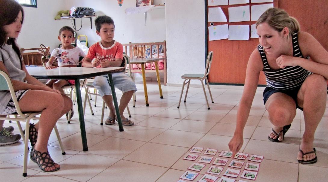 Voluntaria enseñando inglés con recursos didácticos en escuela argentina.